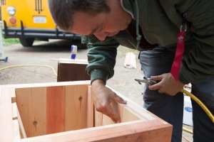 Sean inspects his work and blows away sawdust on the redwood and cedar enclosure